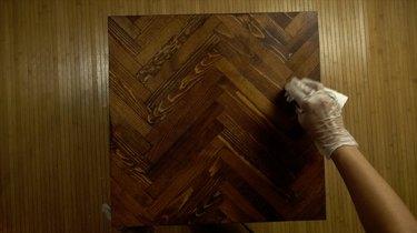 Staining DIY herringbone pattern tabletop using paint sticks.