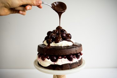 Spoon drizzling chocolate ganache over the top of the Black Forest cake.
