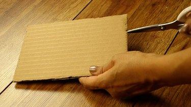 Cutting notches into a DIY cardboard weaving loom.