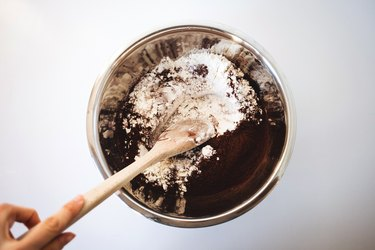 Mixing the dry ingredients in a bowl with a wooden spoon.