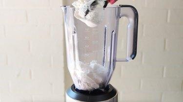 Ice cream being placed in blender jar.