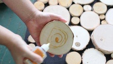 Applying wood glue to log slices