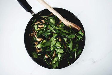 Greens mixed in with mushrooms.