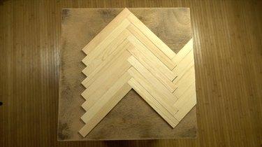 Gluing paint stir sticks to tabletop in herringbone pattern.
