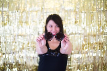Woman holding out sunglasses in front of a gold backdrop
