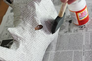 Apply a thin layer of decoupage glue to the exterior of the bust.