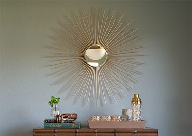 A gold sunburst mirror over on a gray wall