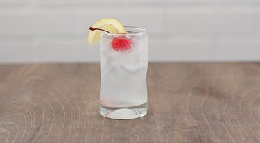 tom collins cocktail garnished with lemon and cherry