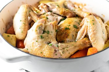 A dutch oven full of roasted chicken, potatoes and carrots
