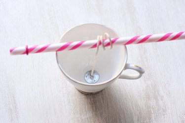 wick glued to bottom of teacup with excess length wrapped around drinking straw