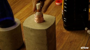 DIY concrete tabletop tiki torches out of used glass bottles.