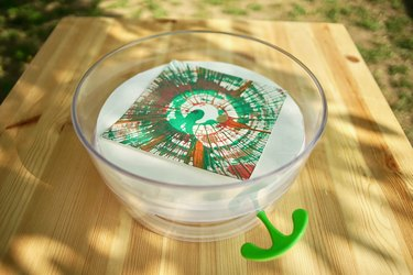 A salad spinner spin art machine stands on an outdoor table
