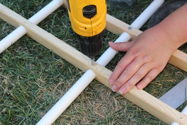 Securing the PVC into the wood with a screw.