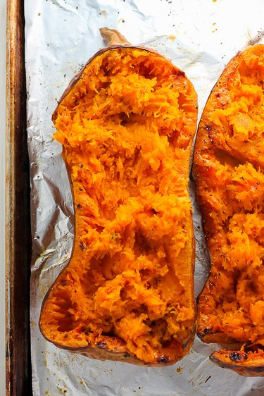 Roasted butternut squash shredded with a fork.