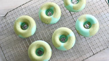 Blue and green donuts cooling on rack