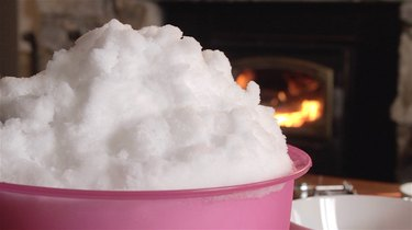 A bowl of fresh snow stands on a table in front of a fireplace.