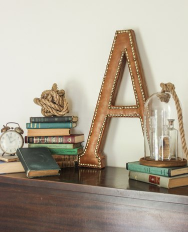 """Monogram  leather """"A""""staged with vintage books, vintage clock, rope ball, and glass cloche."""