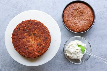 Two carrot cakes with bowl of frosting