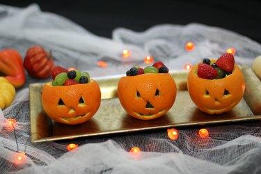 Three jack o'lantern fruit cups on a platter
