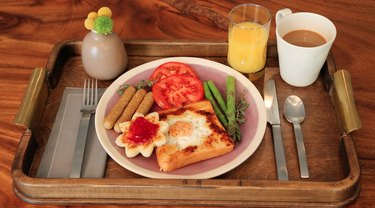 Breakfast in bed tray featuring toad-in-the-hole with sausage, tomatoes, asparagus, juice and coffee