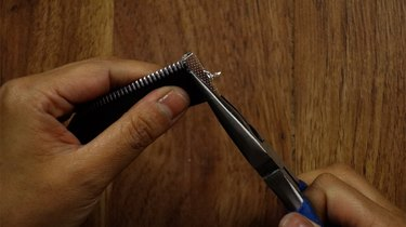 Clamping end of unfinished braided zipper bracelet.