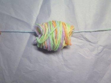Lay the yarn strand underneath the bundle.