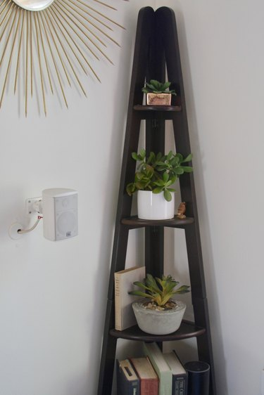 Faux plants on a corner shelf.