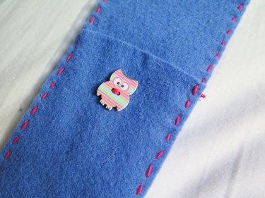 The owl button sewn onto the case.
