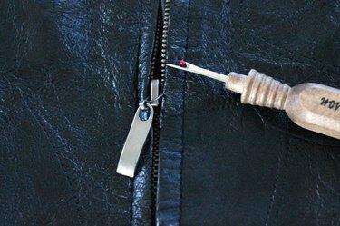 Remove the zipper with a seam ripper.