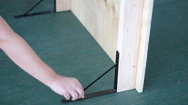 Attaching shelf brackets to bottom of fireplace cover