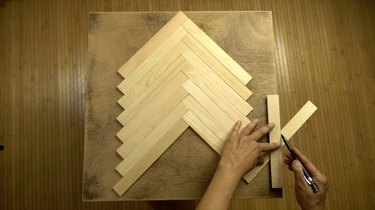 Measuring and cutting paint stir sticks to tabletop to create herringbone pattern.
