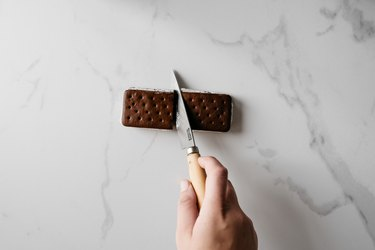 Carefully cut each ice cream sandwich in half.