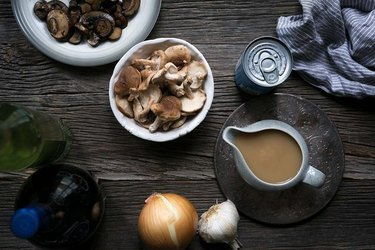 A gravy filled gravy boat next to a bowl of mushrooms, onion, garlic, and a can