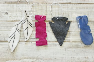 """Two feminine shapes: a pair of white feathers, and a pink block-lettered """"Mom"""" cut-out; and two masculine shapes: a dark gray arrowhead and a blue, block-lettered """"Dad"""" cut-out."""