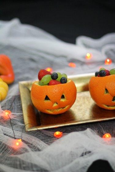 Jack o'lantern fruit cups served on a platter