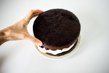 Hand placing the second cake layer over the cream and cherry filling.
