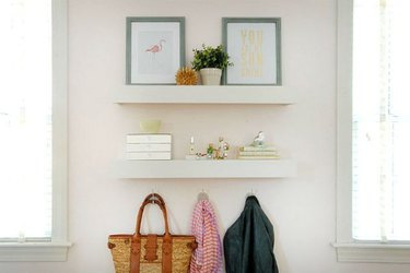 Two white floating shelves over hangers and holding photos and a plant