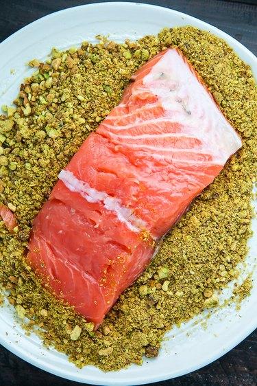 Dip the salmon fillets into the pistachio mixture.