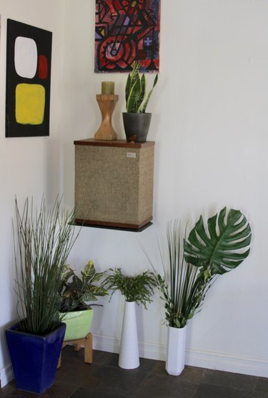 Faux plants in a room with artwork.