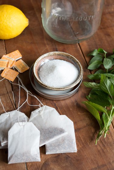 A spread of ingredients for sun brewed tea: tea bags, lemon, sugar and peppermint
