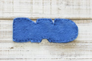 """Both pieces of """"DAD"""" design on felt, sewn together  along perimeter with embroidery thread."""