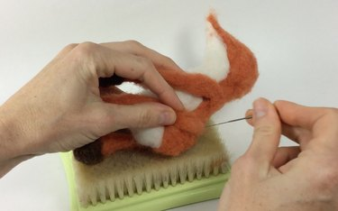 Female hands holding a felting needle while attaching fox limbs