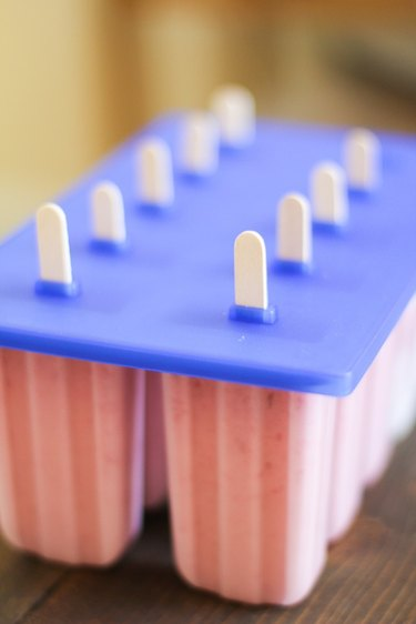 Ice pop molds with sticks ready to freeze.