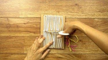 Removing weaving from cardboard loom.