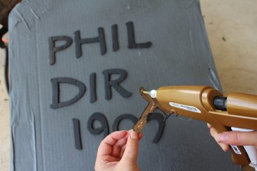 Gluing the letters to the tombstone.