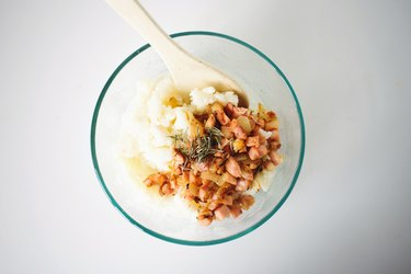 Spoon combining the onion and bacon with the potato in a glass bowl.