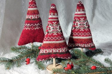 Three red sweater trees surrounded by branches