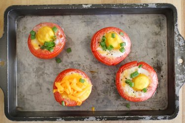 A baking sheet with eggs baked inside tomatoes.