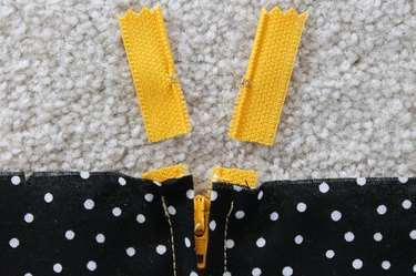 Cut the extra zipper off above the stitches.