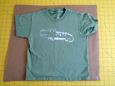 A T-shirt flat on a piece of brown paper.